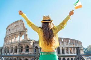 mulher com bandeira italiana, regozijando-se perto do Coliseu, em Roma, Itália