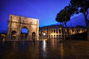 Coliseu e arco de Constantino à noite foto