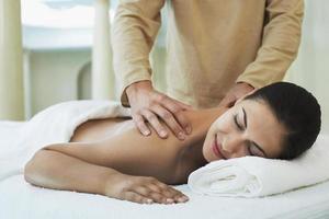 mulher recebendo massagem nos ombros por massagista foto