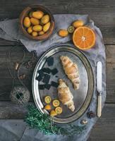 conjunto de café da manhã rústico: croissants de chocolate no prato de metal, frescos foto
