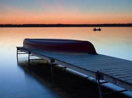 canoa e pescadores ao pôr do sol