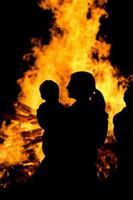 mãe segurando filho assistindo fogueira