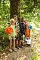 grupo de crianças ao ar livre com equipamento de campismo foto