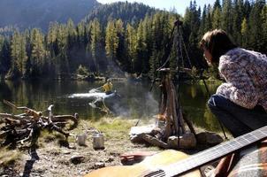 homem e mulher acampar no lago foto