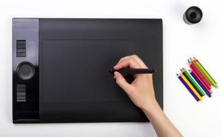mão feminina usando tablet gráfico. criatividade