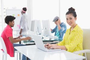 jovem mulher criativa usando o laptop na mesa foto