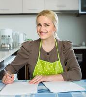 mulher com documentos na cozinha foto