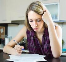 mulher séria com documentos na cozinha foto