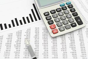 calculadora, caneta, documentos com números e diagrama foto