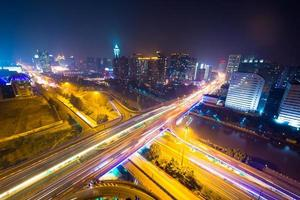 trilhas de semáforo no viaduto e paisagem urbana à noite