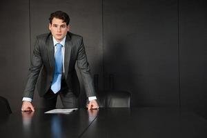 empresário, apoiando-se na mesa de conferência com documentos foto