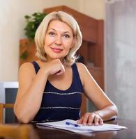 mulher madura com documentos financeiros foto