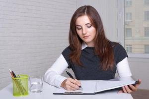 menina senta-se em uma estação de trabalho escreve na pasta do documento foto