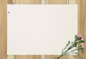 papel branco em branco e cravo rosa sobre fundo de madeira foto