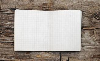 caderno em branco aberto na madeira do grunge foto
