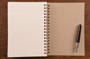 caderno e caneta abertos foto