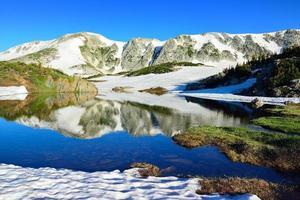 montanhas nevadas e lago alpino com reflexão foto