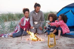 família acampar na praia e brindar marshmallows foto