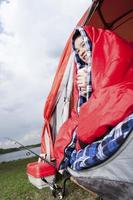 adolescente sentado na tenda aquecendo foto