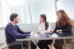 três empresários discutindo algo juntos foto