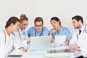 médicos e enfermeiros discutindo informações sobre um laptop foto