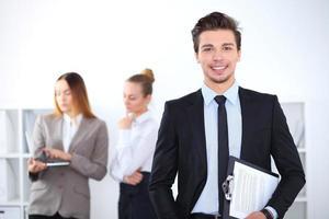 homem de negócios alegre no escritório com colegas no fundo foto