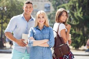 jovens amigos atraentes estão indo para a universidade