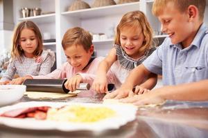 crianças fazendo pizza juntos