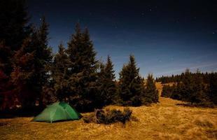 tenda iluminada com luz na floresta à noite foto