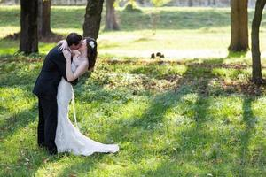 elegante noiva e noivo posando juntos ao ar livre foto