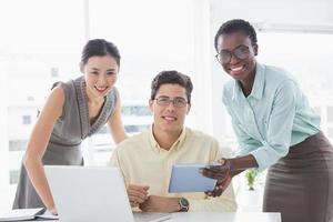 equipe de negócios casuais olhando tablet juntos foto