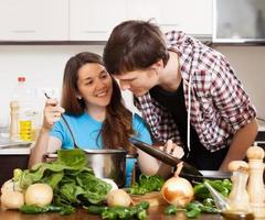 homem e jovem mulher cozinhando juntos