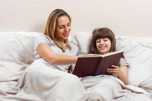 mãe e filha lendo juntos livro na cama