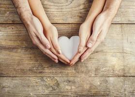 mãos de homem e mulher segurando um coração juntos. foto