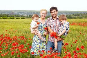 jovem família feliz de quatro se divertindo juntos ao ar livre.