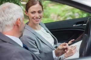 parceiros sorridentes trabalhando juntos no carro elegante