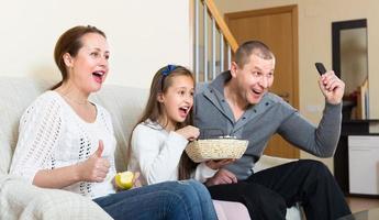 família assistindo programa de tv foto