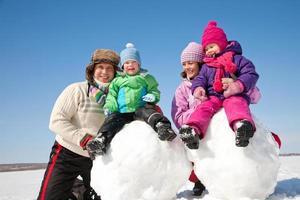 família feliz fazendo boneco de neve foto