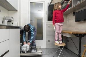 família esvaziando a máquina de lavar louça foto