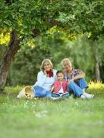 família com maçãs e livro no parque