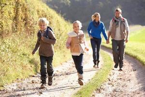 família jovem caminhando no parque foto