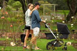 família jovem andando com carrinho foto