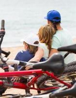 família com bicicletas na praia foto