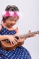 criança tocando ukulele / criança tocando ukulele fundo foto