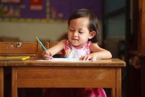 criança escrevendo e sorrindo foto