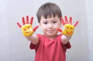 criança com as mãos pintadas foto