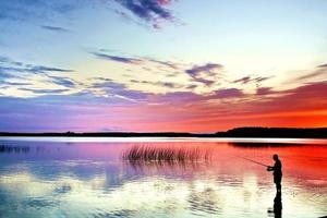 pescador com vara na beira do lago ao pôr do sol