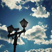 sol escondido por um poste de luz. foto envelhecida.