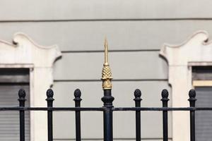 portão preto com uma ponta dourada foto