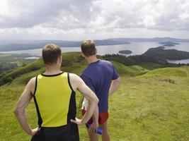 homens na colina, olhando para o lago foto